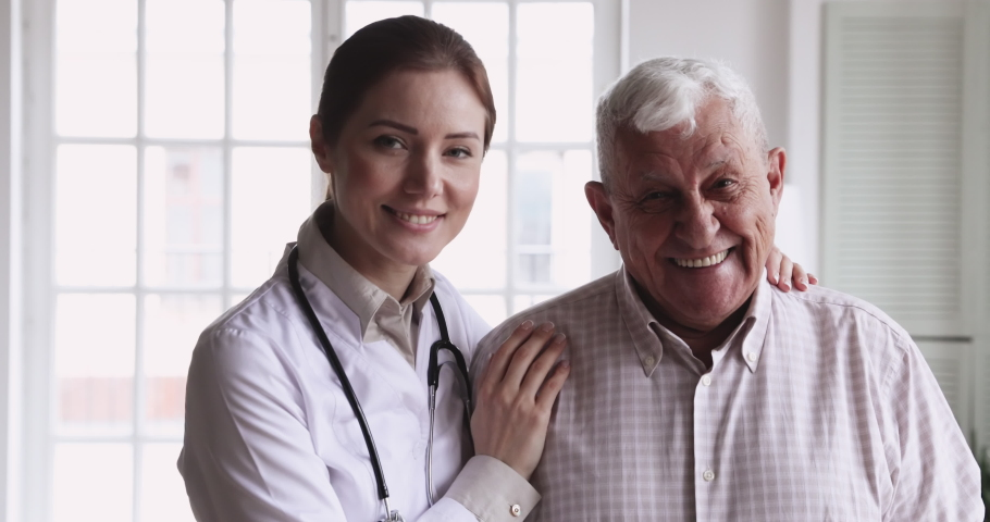 Smiling young female doctor physician wear white coat stethoscope embrace happy senior elder patient look at camera in hospital. Eldercare, old people healthcare medic service concept, close up
