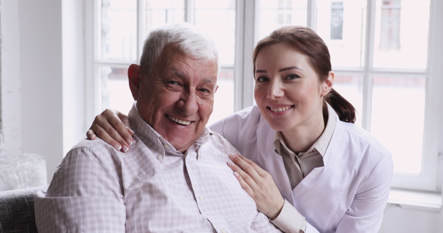 Caring smiling female caregiver embracing happy senior patient looking at camera. Young carer or nurse helping old elder care grandpa at nursing home, geriatric medical support concept, closeup