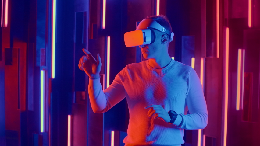 Futuristic virtual reality, a man in a helmet and neon light moves his hands while in virtual reality #1047429517