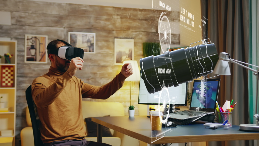 Engineer with VR headset working in virtual enviroment to design a new turbine in a cozy home office. Hologram effect | Shutterstock HD Video #1047443674