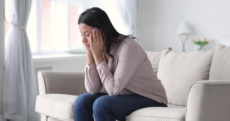 Depressed unhappy frustrated young african american woman suffer from mental stress shame anxiety sit alone on sofa at home. Upset worried millennial lady feel desperate regret bad mistake concept | Shutterstock HD Video #1047458482