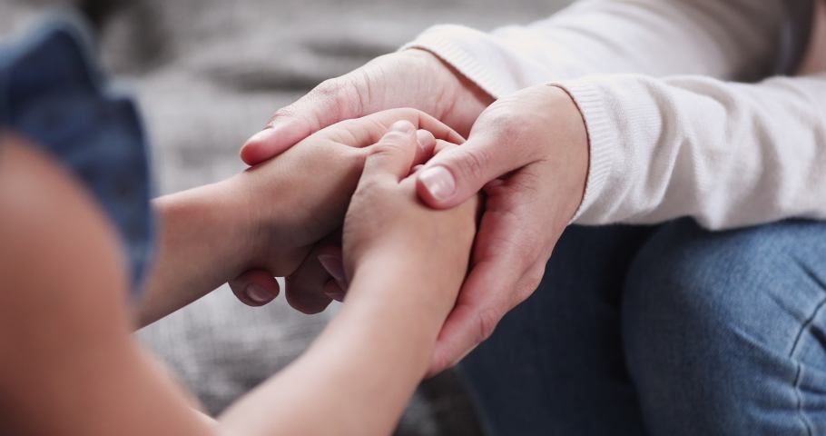 Adult mother volunteer holding hands of kid girl close up view. Foster care parent protect small child daughter give hope love care support concept. Children patient health donation charity adoption Royalty-Free Stock Footage #1047458560