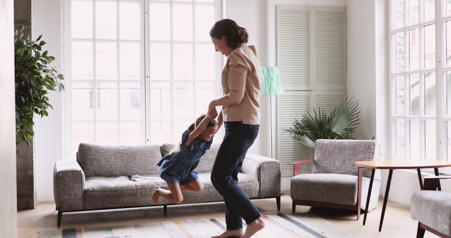 Mature older grandmother dance with energetic child girl in living room. Active old grandma and grandkid having fun spin around. Happy middle aged nanny play with cute small kid granddaughter at home #1047458593