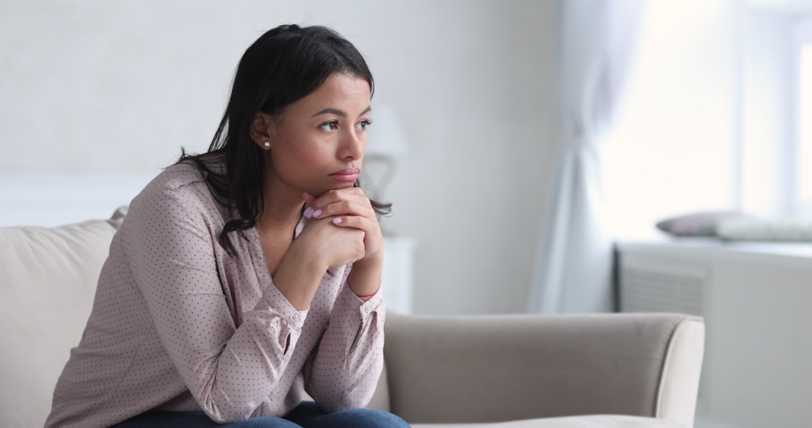 Sad thoughtful young african american single woman pensive face looking away thinking of problems sit alone at home, upset mixed race ethnic lady feeling depressed reflecting feel lonely concept.