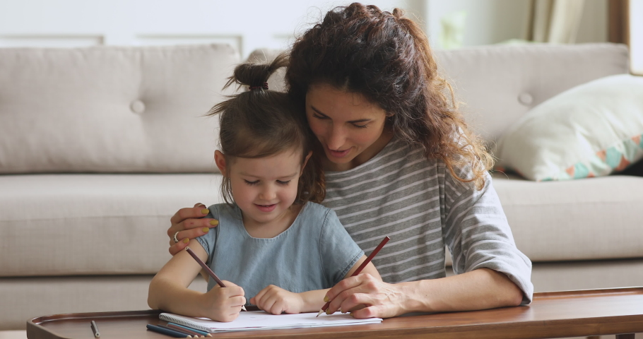 Affectionate young woman babysitter cuddling small cute kid daughter, drawing pictures together in paper album. Happy family of two enjoying creative time together, sitting at coffee table on floor.