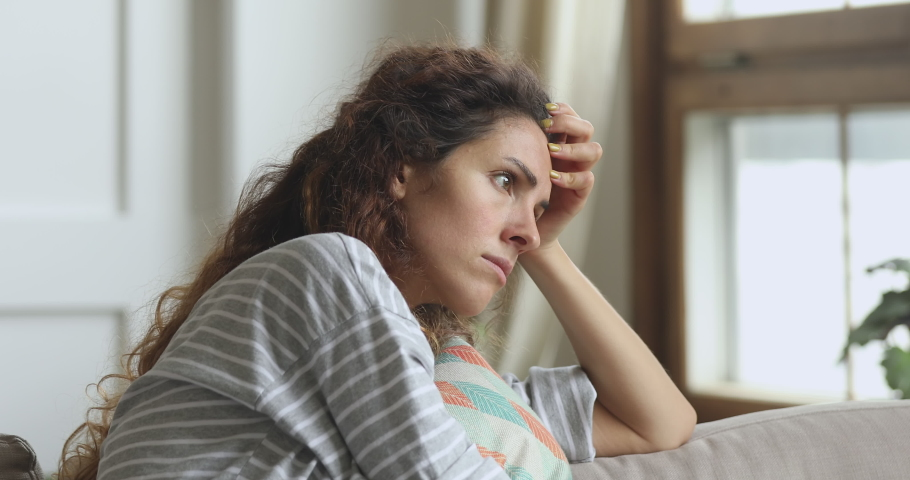 Nervous young woman embracing pillow, feeling unsure about hard decision, sitting alone on sofa. Depressed lady regretting mistake abortion, suffering from psychological problem trouble at home. | Shutterstock HD Video #1047476635