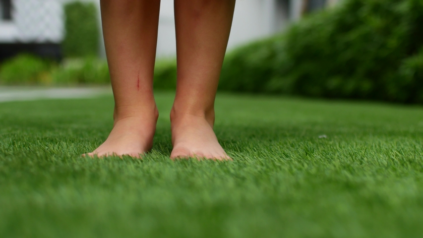 Bare feet on the grass. The green grass in the park beckons to be barefoot #1047477334