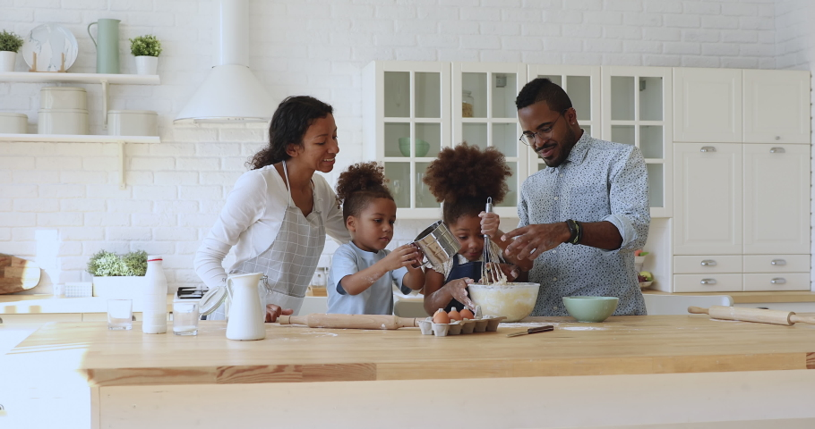 Happy african ethnicity young couple parents watching kids siblings mixing eggs with flour, using whisk at modern kitchen. Joyful full family having fun, enjoying cooking process on weekend at home. #1047481825