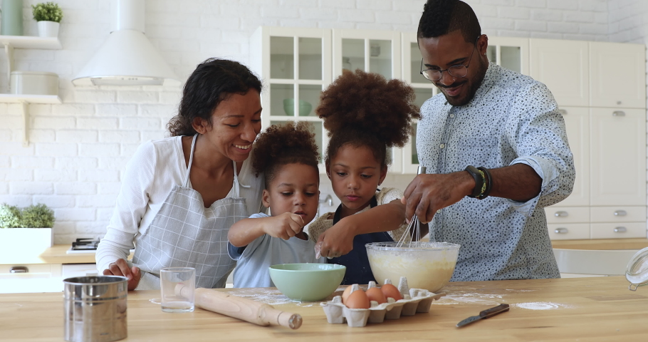 Happy full family having fun preparing pastry together at home. Smiling african dad whisking mixture in bowl while joyful little children adding flour, cooking homemade baking together at kitchen. Royalty-Free Stock Footage #1047485464