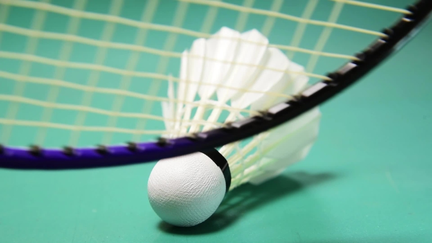 moment of badminton racket scooping shuttlecock from court ground