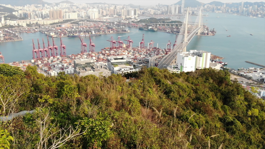 Stonecutters Bridge span across Rambler Channel, view from south peak of Tsing Yi island, drone shot. Container terminal facilities on reclaimed land | Shutterstock HD Video #1047515674