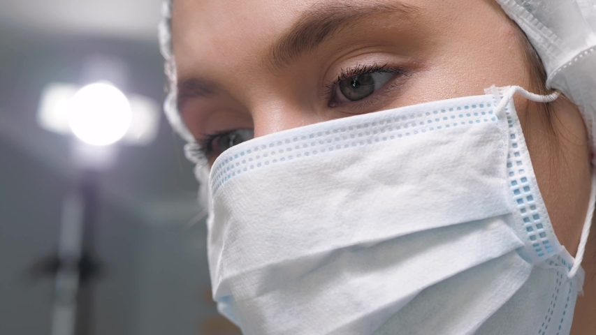 Girl surgeon doctor in surgical mask looks down at patient and then to side at monitor or assistants. Operation, practitioner, operating room, surgery, transplantation, medicine concept. Close-up