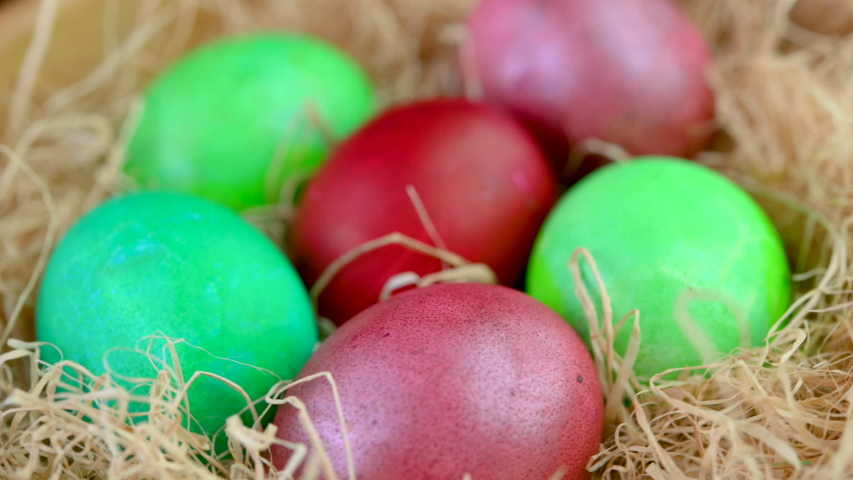 Closeup top view Colorful easter eggs lie on a bacon in a basket. 360 rotation. Easter decorations. Easter concept background. | Shutterstock HD Video #1047520657