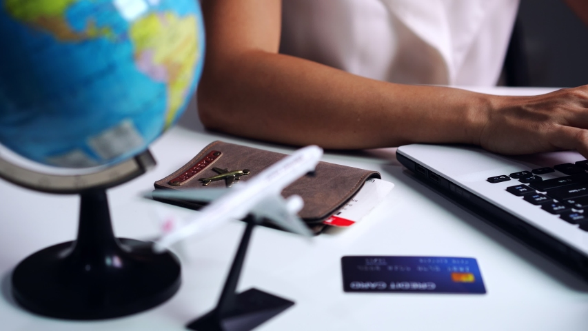 Young woman holding credit card and planning vacation trip with laptop, Travel planning concept | Shutterstock HD Video #1047522946