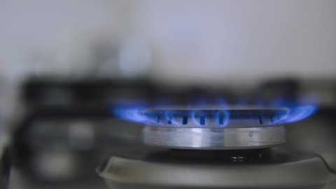 Kitchen burner turning on.Stove top burner igniting into a blue cooking flame.