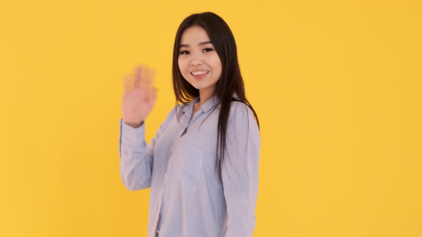 Young Asian girl on a yellow background waving at the camera. the woman welcomed. | Shutterstock HD Video #1047537289