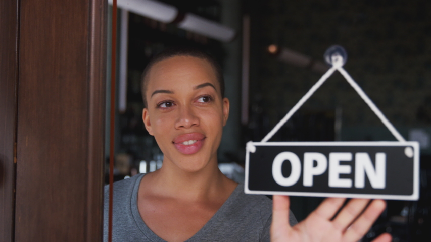 Female owner of coffee shop or restaurant walking up to door and turning round sign to open - shot in slow motion Royalty-Free Stock Footage #1047538543