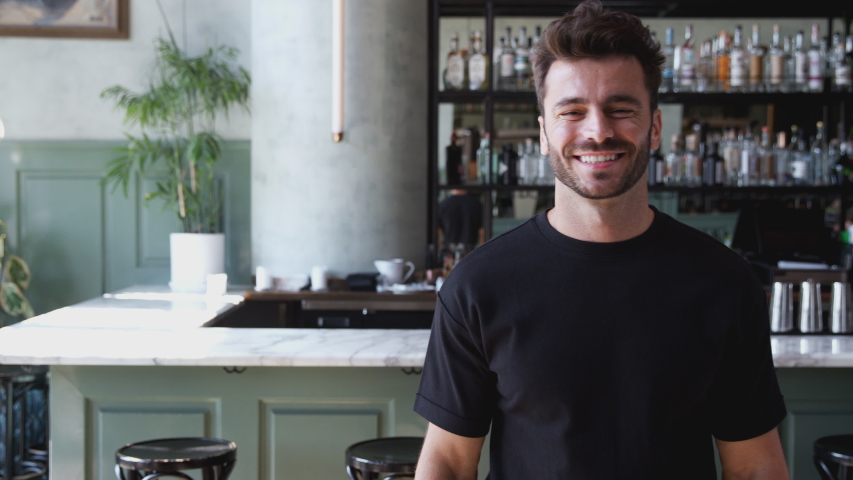 Portrait of male owner of restaurant bar standing by counter smiling and looking confident - shot in slow motion Royalty-Free Stock Footage #1047538579