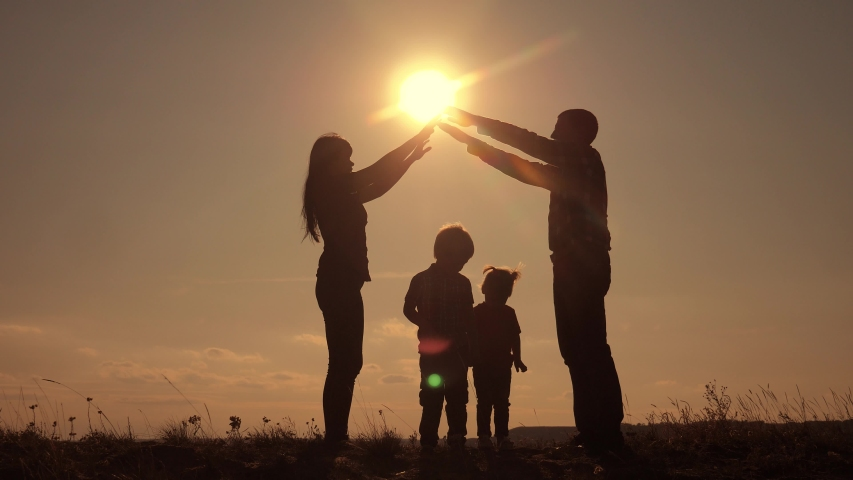 happy family teamwork silhouette shows a house and comfort symbol home at sunset. happy family mom dad and kids children portray a house roof hold their hands lifestyle over their heads home #1047542350