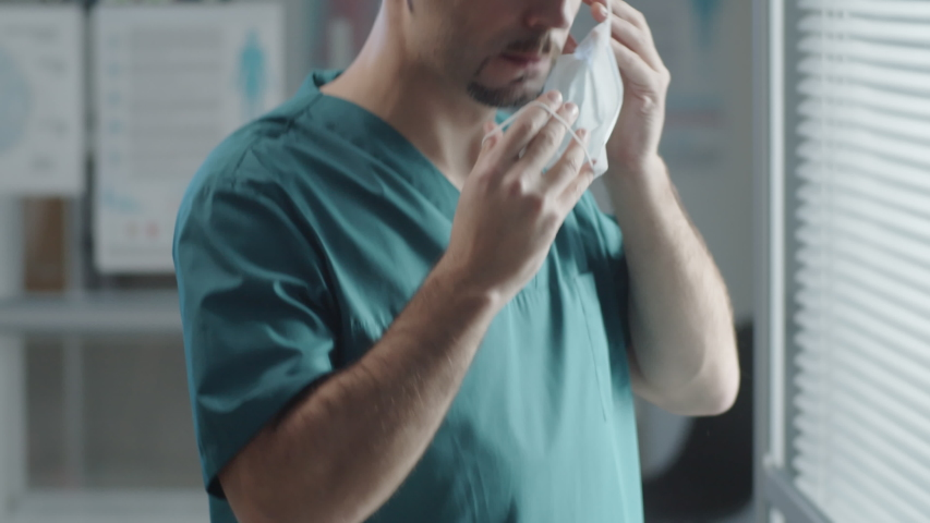 Tilt up shot of male hospital worker in scrubs and disposable hat putting medical mask on face and walking away | Shutterstock HD Video #1047544084