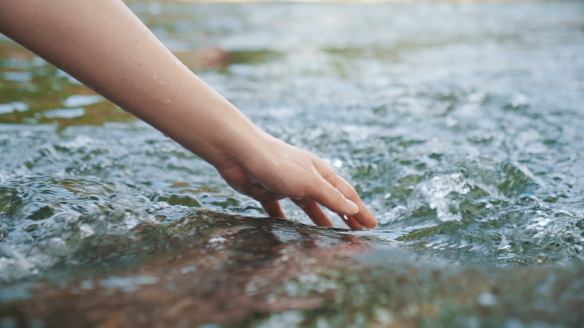 Hand touching water in the forest river or lake. People travel enjoying nature and life concept. Royalty-Free Stock Footage #1047550183