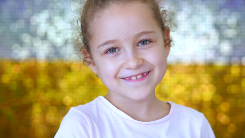 Portrait of a little young girl with green eyes looks at the camera, against a background of white and gold shiny glow. Portrait of a funny baby or child smiling, looking at camera. Royalty-Free Stock Footage #1047569230
