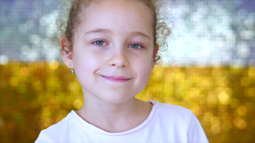 Portrait of a little young girl with green eyes looks at the camera, against a background of white and gold shiny glow. Portrait of a funny baby or child smiling, looking at camera. Royalty-Free Stock Footage #1047569236
