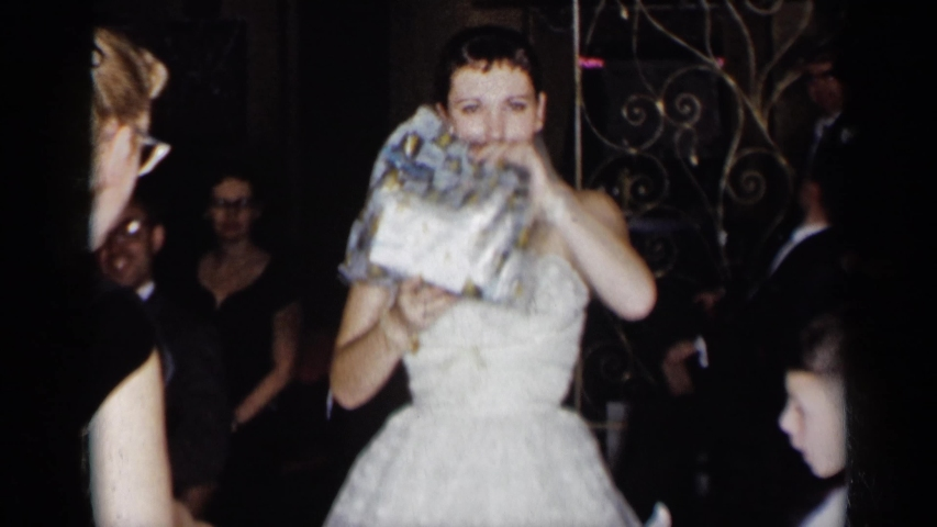 NEW YORK-1954: Bride Wearing White Dress Holds Up A Present While Surrounded By Family And Friends #1047570907