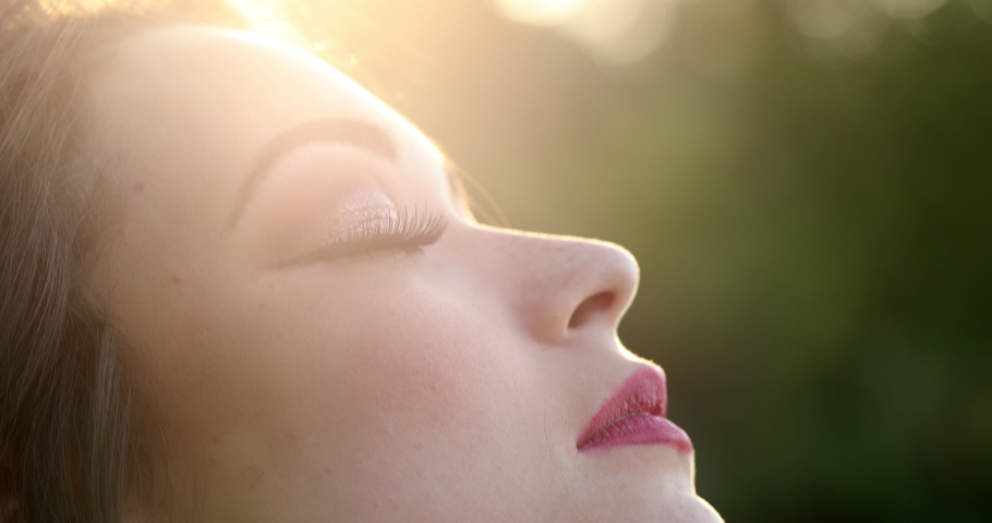 Attractive girl eyes closed outside in the sunlight lens-flare meditating #1047572854
