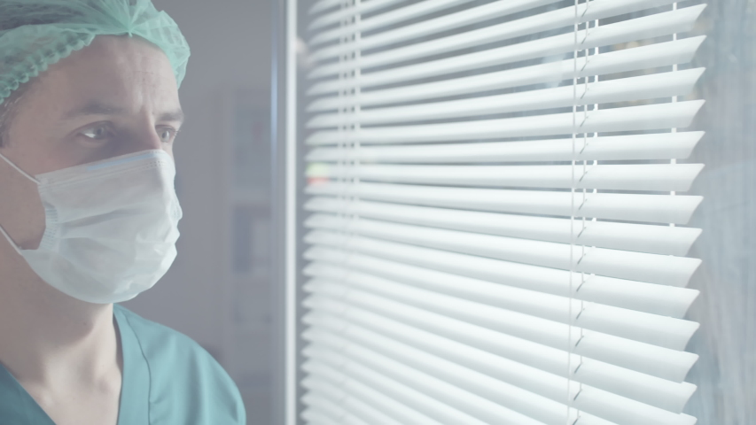 Tracking chest up shot of male medical worker in scrubs and disposable hat taking medical mask off face, looking at camera and smiling | Shutterstock HD Video #1047573349