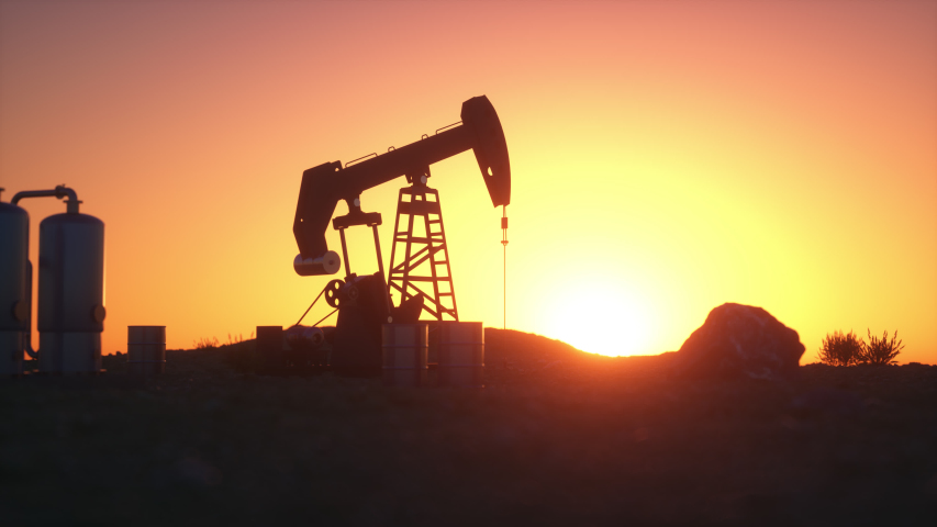 Oil pump jack in the desert as the sun sets, leaving its silhouette against the sky with refinery tanks, bushes and rocks. Loopable animation.