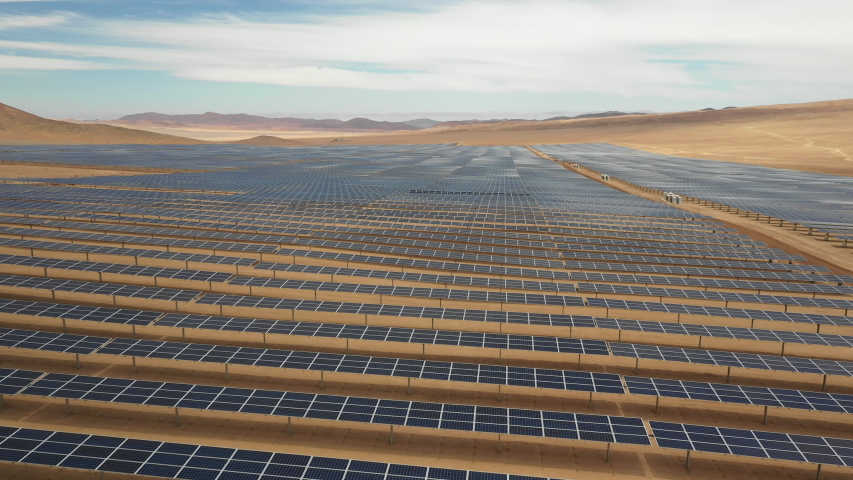 Aerial footage hundreds solar energy modules or panels rows along the dry arid lands at Atacama Desert, Chile. Huge Photovoltaic PV Plant in the middle of the desert from an aerial drone point of view | Shutterstock HD Video #1047590668
