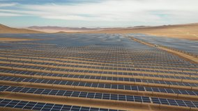 Aerial footage hundreds solar energy modules or panels rows along the dry arid lands at Atacama Desert, Chile. Huge Photovoltaic PV Plant in the middle of the desert from an aerial drone point of view