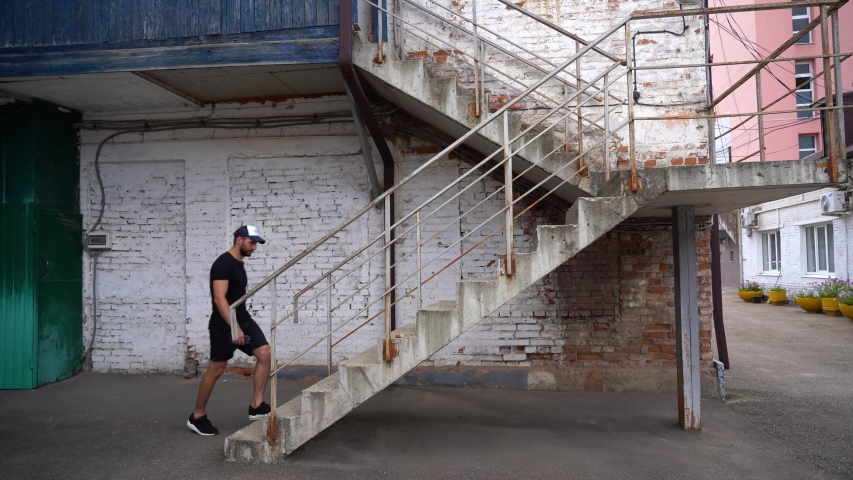 Caucasian bearded man in a black T-shirt shorts and a cap slowly ascends the concrete stairs with rusty railing against white brick wall of old factory on a warm sunny day. Old district of the city. | Shutterstock HD Video #1047605224