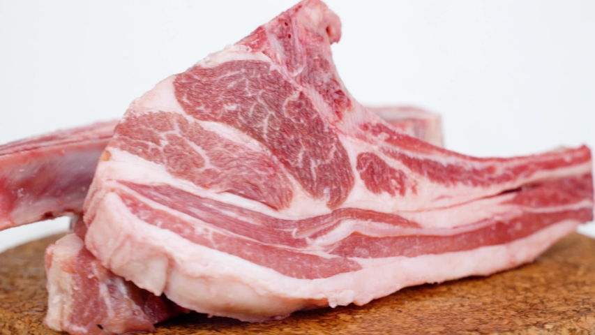 Close up of raw lamb chop spinning on cutting board. Shot in 4k resolution with isolated on white background