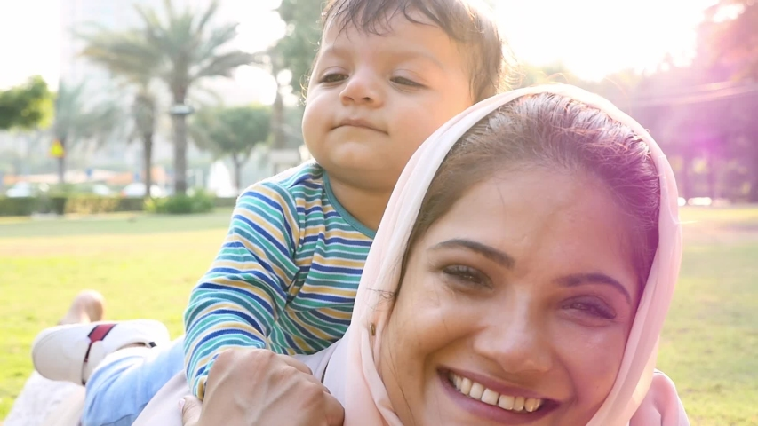 Mother and little son spending time together at the park. Muslim family outdoor in Dubai. Lifestyle moments in the UAE