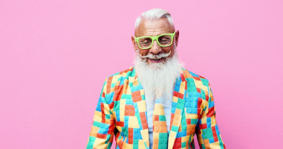 Senior man hipster with funny colored outfit on colored backgrounds