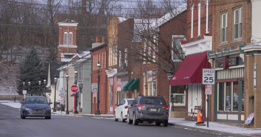 BRIDGEWATER, PA - Circa March, 2020 - A daytime establishing shot of storefronts along a main street in a small town. Church steeple in distance. Snowing version available.   | Shutterstock HD Video #1047628231