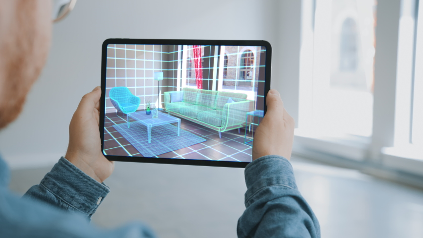 Decorating Apartment: Man Holding Digital Tablet with Augmented Reality Interior Design Software Chooses 3D Furniture for Home. Man Pick Sofa, Table and Lighting for Living Room. Over Shoulder Screen  Royalty-Free Stock Footage #1047633148