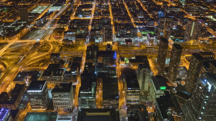4K UHD Hyperlapse time-lapse of car traffic and city building at night in Chicago city downtown. Drone aerial top view, fly upward. Commuter, America city life or public transportation concept
