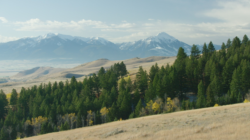 The Absaroka mountains tower above the Paradise Valley and Yellowstone river in a color filled Montana autumn | Shutterstock HD Video #1047648607