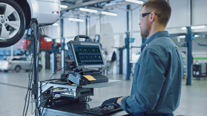 Car Service Manager or Mechanic is Running an Interactive Diagnostics Software on an Advanced Computer. Specialist Inspecting the Vehicle in Order to Find Broken Components and Errors in Data Logs.