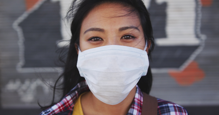 Portrait of a mixed race woman with dark hair out and about in the city streets during the day, wearing a face mask against air pollution and Coronavirus Covid19, looking at camera