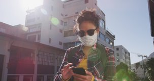 Low angle front view of a mixed race woman with long dark hair out and about in the city streets during the day, wearing sunglasses and a face mask against air pollution and Coronavirus Covid19