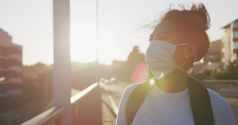 Front view of a mixed race woman with long dark hair out and about in the city streets during the day, wearing a face mask against air pollution and coronavirus Covid19, walking and using a smartphone