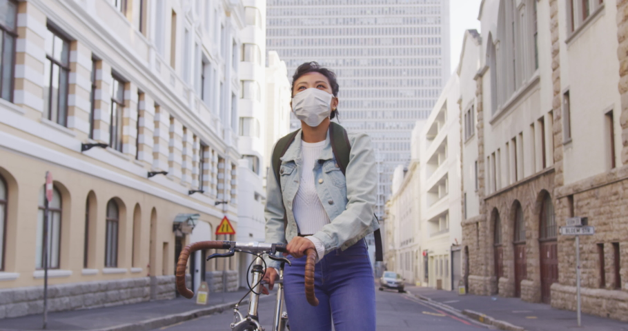 Front view of a mixed race woman with long dark hair out and about in the city streets during the day, wearing a face mask against air pollution and coronavirus Covid19, walking with her bicycle | Shutterstock HD Video #1047706960