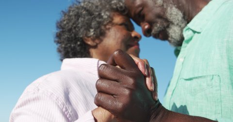 Low angle side view close up of a senior African American couple standing on the beach with blue sky in the background, holding hands, dancing and having fun in slow motion