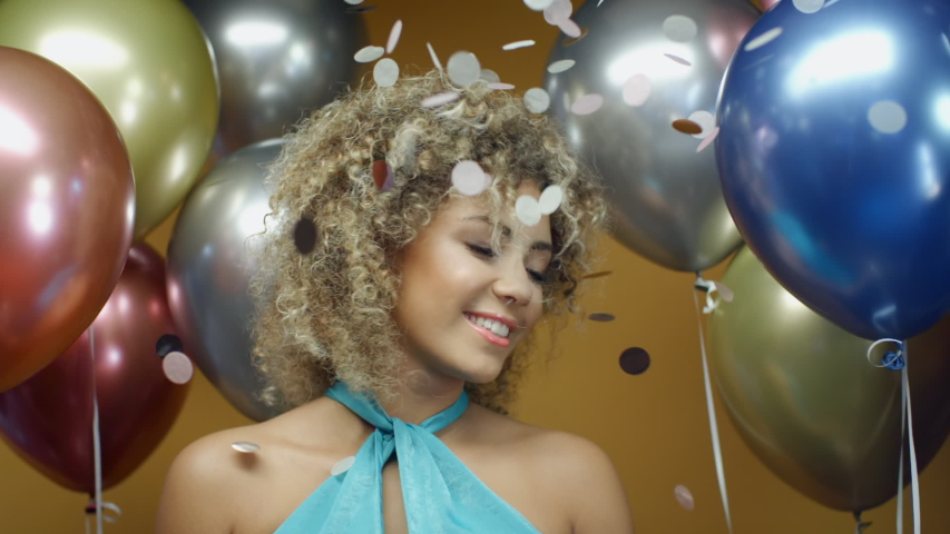 Beautiful curly hispanic woman in turquoise dress dancing on yellow background with multicolored balloons and flying confetti in slow motion. Pretty mixed race girl celebrates holiday at summer party
