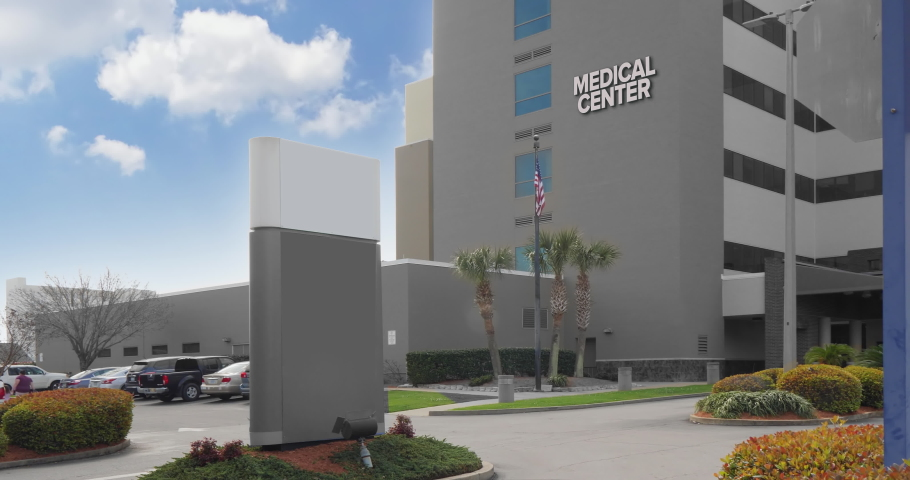 A daytime summer exterior establishing shot of a typical city Medical Center emergency room entrance.  Summer, day. Blank sign for customization.