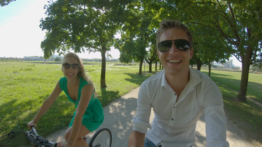 SLOW MOTION, LENS FLARE, SELFIE: Adorable young tourist couple ride their bikes down a scenic sunlit avenue in a park in Ljubljana. Caucasian girl and her boyfriend smile while riding their bicycles. Royalty-Free Stock Footage #1047721510